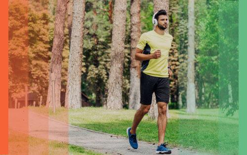 Un homme seul court dans un parc en écoutant de la musique